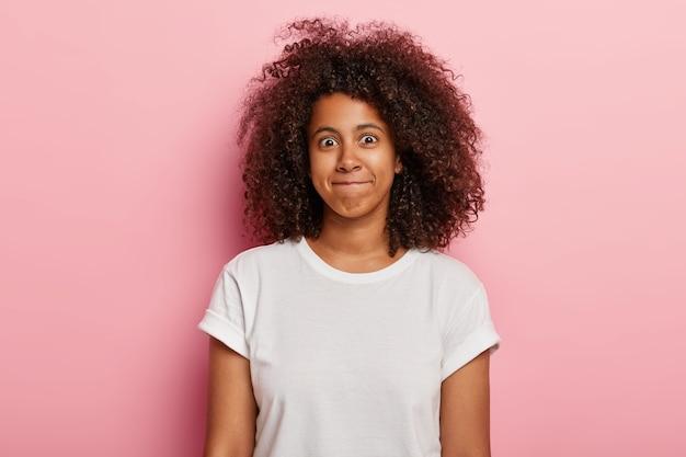 面白い女性の写真は、巻き毛の太い髪、唇を一緒に押し、幸せそうな顔をしていて、白いtシャツを着て、ピンクの壁に隔離されています。格好良い若いアフリカ系アメリカ人の女の子は幸せを表現します。