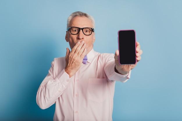 スマートフォンの新しいモデルを示す紳士の写真