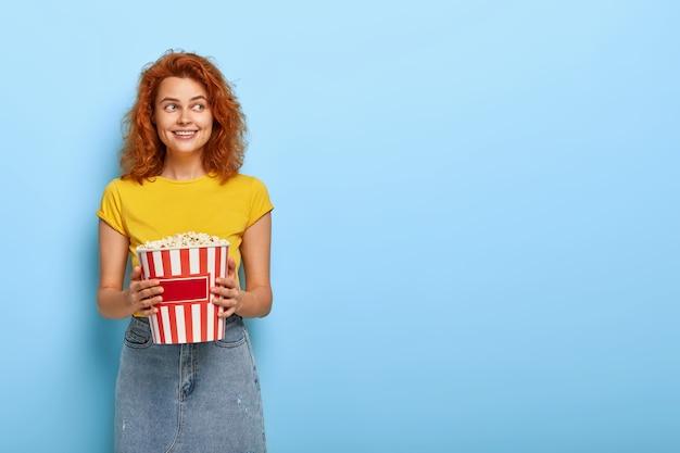 生姜の魅力的な女の子の写真はポップコーンでバケツを保持します