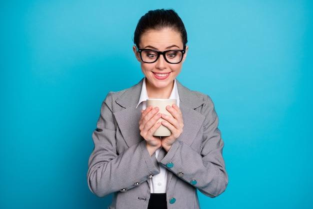 Фотография девушки-маркетолога с кружкой напитка в сером костюме, пиджаке, пиджаке, изолированном на синем цветном фоне