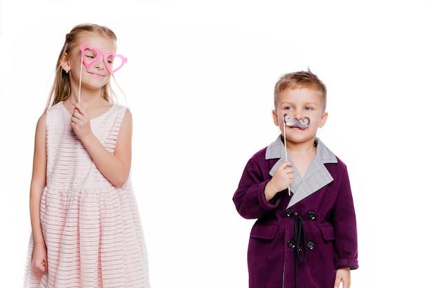 ハート型の段ボールグラスを持つ少女とポーズをとる段ボールの口ひげを持つ少年の写真