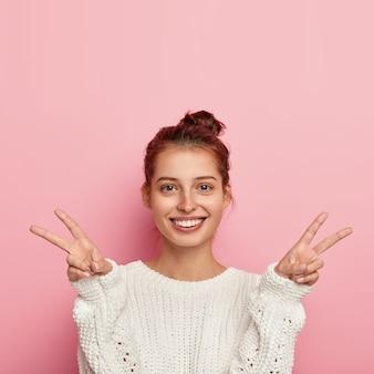 喜んでいるヨーロッパの女性の写真は広く笑顔で、両手で平和の勝利のジェスチャーをし、優しい表情をして、ニットの白いセーターを着て、熱意を表現し、幸福の兆候を示し、ピンクで隔離されています