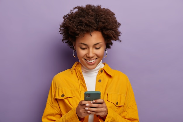 스마트 폰에 초점을 맞춘 기쁜 여성의 사진은 노란색 셔츠를 입고 부드럽게 미소를 짓고 보라색 스튜디오 벽 위에 절연되어 있습니다.