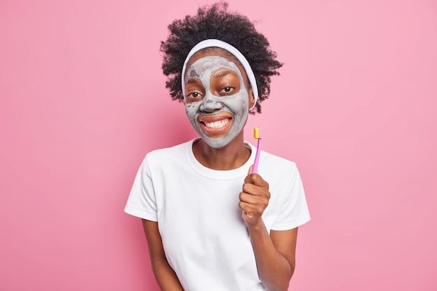 アフロの髪の笑顔を持つ嬉しいミレニアル世代の女の子の写真は、心地よく粘土マスクを適用し、歯ブラシを保持しています
