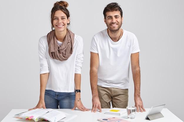 기쁜 젊은 여성 및 남성 학생의 사진은 테이블에 기대어