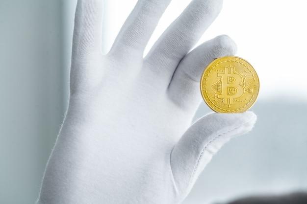 Фото золотых биткойнов с виртуальными монетами в руке