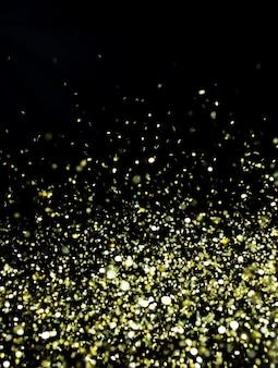 Фото золотого блеска на черном фоне. золотой взрыв конфетти. праздничный фон
