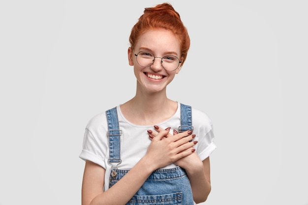 格好良いポジティブな女性の写真は、両手を心に留め、心地よい笑顔を持ち、感謝の気持ちを表します