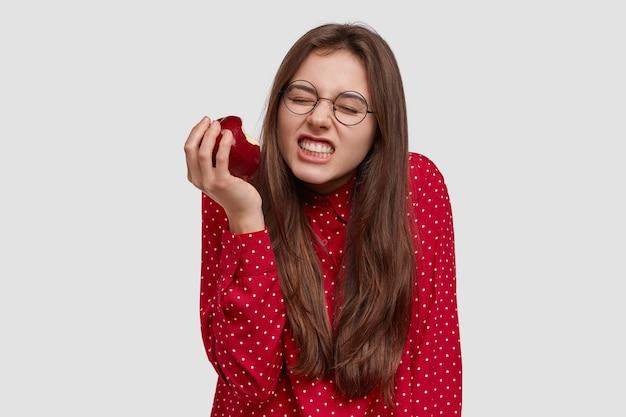 Фотография красивой женщины, стиснутой зубами, кусающей свежее красное яблоко, одетой в элегантную рубашку, носит очки