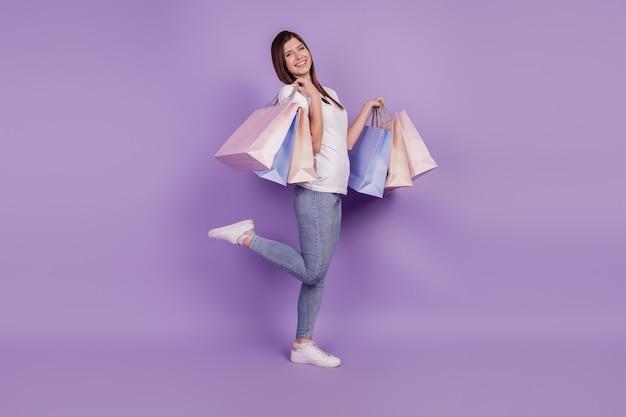 좋은 분위기의 여성이 쇼핑 팩을 들고 있는 사진은 보라색 배경에 격리되어 있습니다.