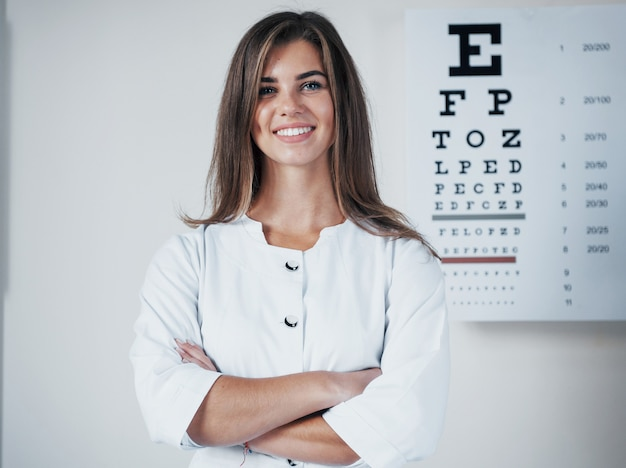 Фотография великолепного офтальмолога-женщины, позирующего за доской с буквами.