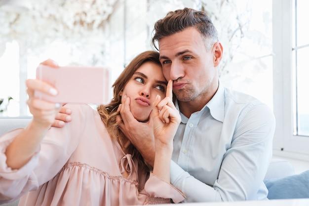 Фото великолепной прекрасной пары делает селфи на мобильном телефоне и дурачится, имея дату в ресторане