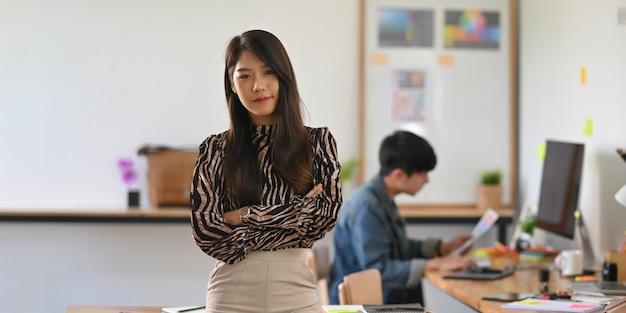 Фото девушки график-дизайнера стоя с рукой пересекло на деревянный рабочий стол над ее коллегой и удобной художественной студией.