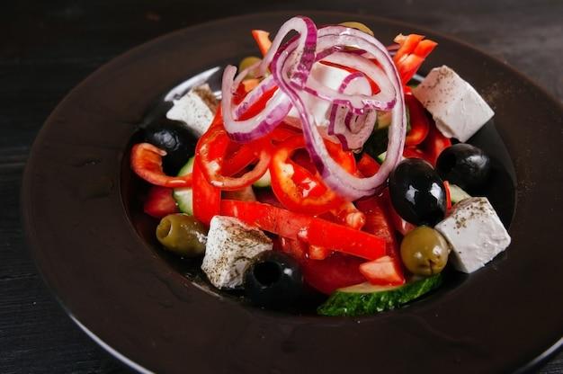 黒いプレートのギリシャ風サラダの写真。