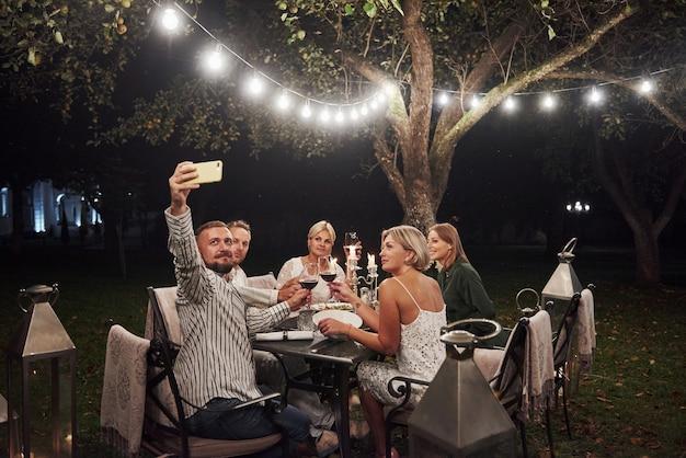 Фото парень принимает селфи. группа друзей в элегантной одежде имеют роскошный ужин
