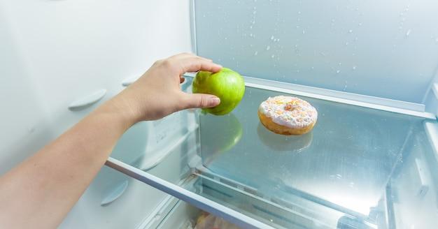 Фотография руки, держащей яблоко вместо пончика, лежащего в холодильнике