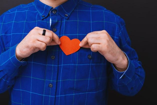 小さな紙を保持しているhandome男性の写真は、胸、愛の概念、暗い分離baackgroundの上に立って聞く