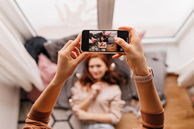 Фотография рук, держащих смартфон и фотографирующих. крытый портрет рыжеволосой дамы, позирующей для своего друга.
