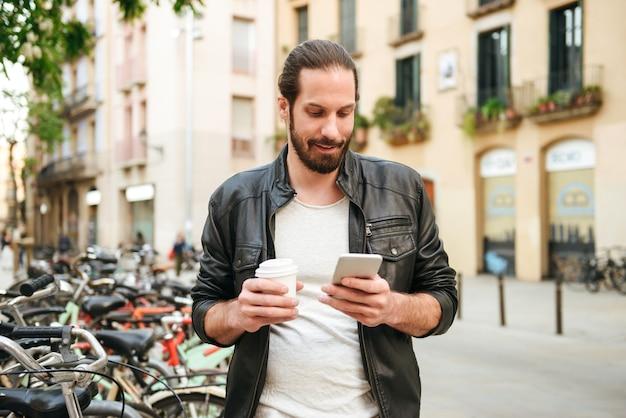 테이크 아웃 커피를 마시고 시내에서 휴대 전화를 사용하는 캐주얼 한 옷을 입고 잘 생긴 성인 남성 30 대 사진