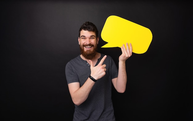 暗い背景の上に黄色の泡のスピーチを指しているハンサムなひげを生やした男の写真