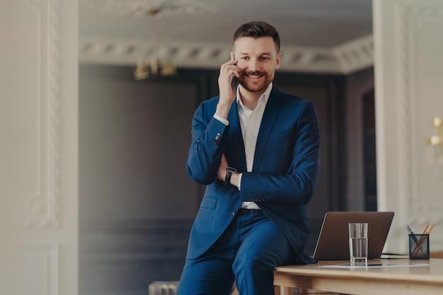 Фотография красивого бородатого мужчины разговаривает по телефону, устраивает сотовый звонок с хорошими новостями, позирует на рабочем столе с современным портативным компьютером, одетым в синий деловой костюм. мобильный разговор