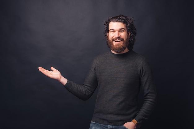 Фото красивого бородатого мужчины, держащего copyspace в ладони