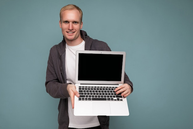 Фотография красивого блондина, держащего компьютерный ноутбук, смотрящего в камеру, изолированного на синем фоне стены, в белой футболке и сером свитере