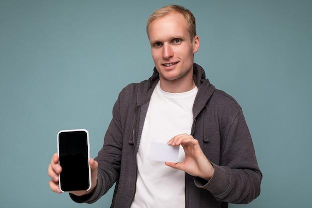Фотография красивого блондинки в сером свитере и белой футболке, изолированных на синем фоне стены, держащей кредитную карту и мобильный телефон с пустым экраном для макета, смотрящего в камеру.