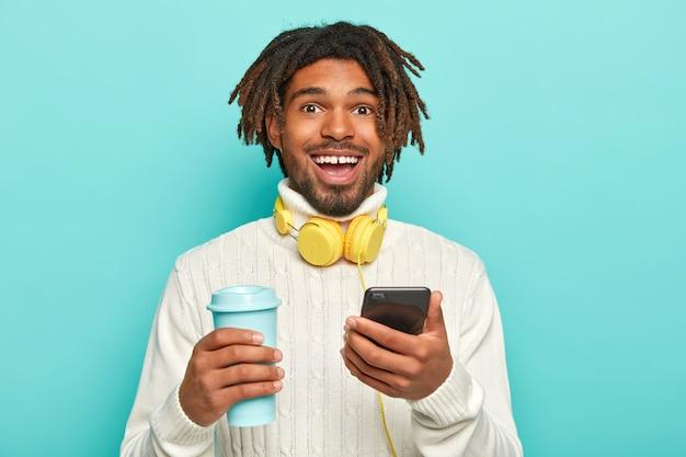 ドレッドヘアを持つハンサムな陽気な男の写真は、ヘッドフォンで、現代の携帯電話とテイクアウトコーヒーを保持します