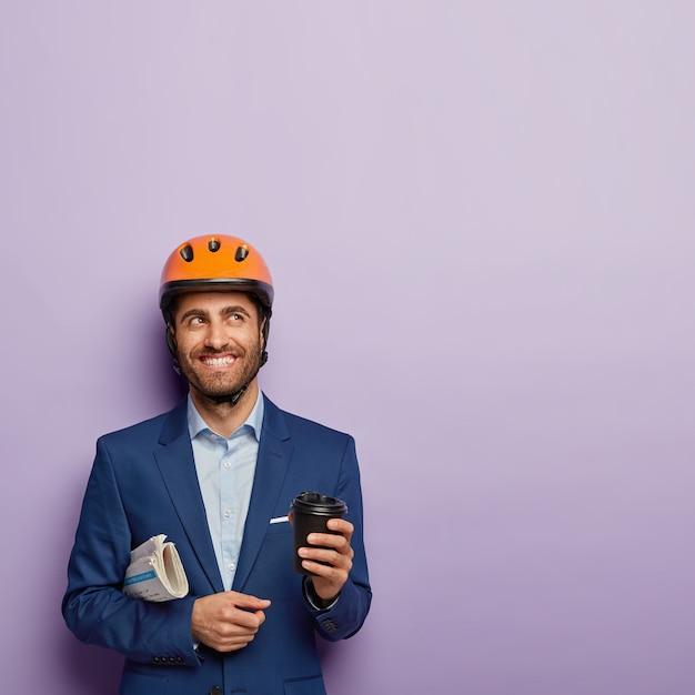 歯を見せる笑顔でハンサムな陽気な男の写真、しわくちゃの新聞を運び、テイクアウトコーヒーを保持し、新しい成功した建築プロジェクトについて考え、保護ヘルメットを着用し、フォーマルなスーツ
