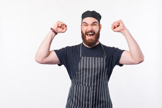 성공을 축 하하는 수염을 가진 잘 생긴 요리사 남자의 사진