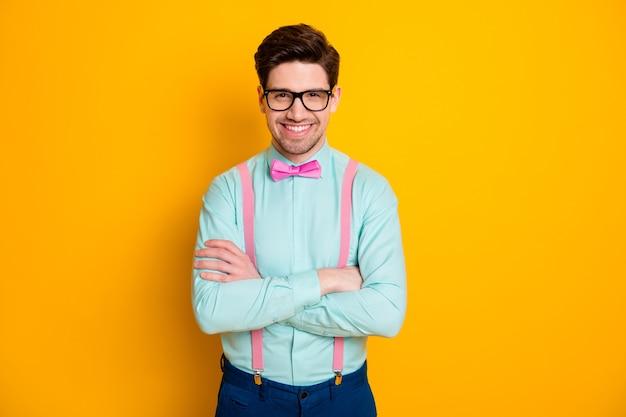 잘 생긴 멋진 옷 비즈니스 남자의 사진은 자신감이 손을 넘어 빛나는 미소 착용 사양 셔츠 멜빵 나비 넥타이 바지 절연 노란색 배경의 사진