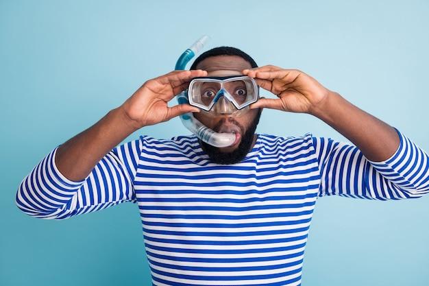 ハンサムな面白い暗い肌の男の観光客ダイビング水中マスクの写真カラフルな魚のサンゴの呼吸チューブフローティングディープウェアストライプセーラーシャツ孤立した青い色の壁を参照してください