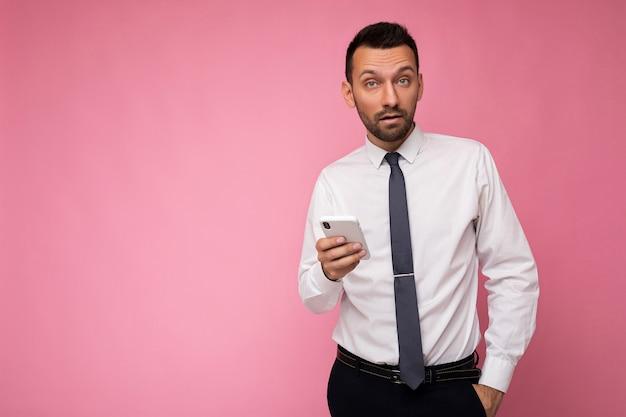Фотография красивого симпатичного человека в повседневной белой рубашке и галстуке, изолированных на розовом фоне с пустым пространством, держащим в руке и использующим смс для обмена сообщениями на мобильном телефоне, глядя в камеру