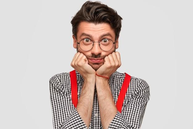 ハンサムな男性のヒップスターの写真は、あごの下に手を置き、直接見て、ファッショナブルなチェックのシャツと赤いブレースを着て、対話者に注意深く耳を傾け、聞いた情報を分析します