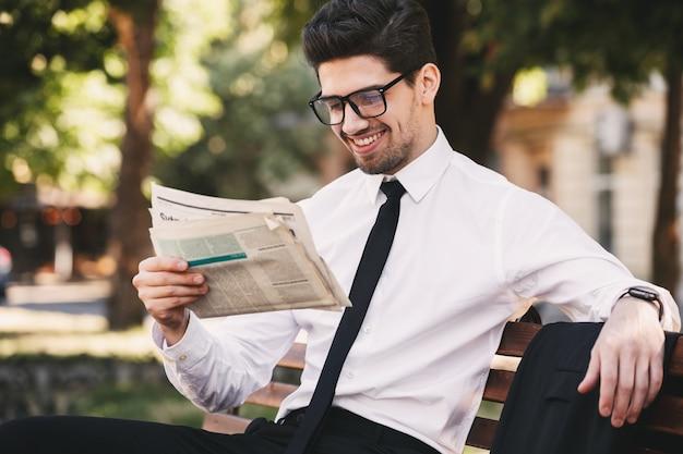 緑の公園のベンチに座って、晴れた日に新聞を読んでビジネスライクなスーツを着たハンサムな男の写真