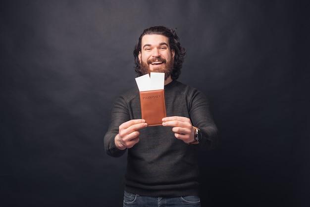 カジュアルな黒の壁の上のパスポートとチケットを示すハンサムな男の写真