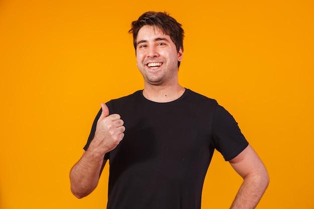 カジュアルな t シャツを着たハンサムな男が親指を立てて笑っている写真。