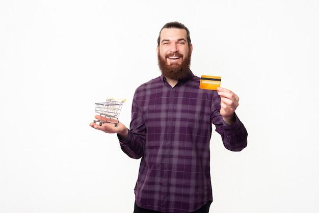Фото красивого мужчины в клетчатой рубашке, держащего небольшую тележку для покупок и кредитную карту