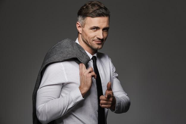 Фотография красивый мужчина в деловом костюме, указывая пальцем и держа пиджак через плечо, изолированных на серую стену