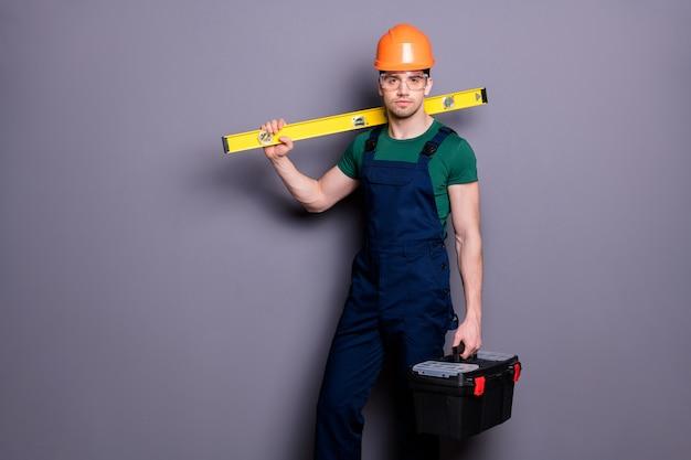 Фотография красивого мужественного парня, опытного инженера, держите измерительную стойку, ящик для инструментов, готовый к работе, одежда, футболка, защитный комбинезон, защитный шлем, очки, изолированные серая стена
