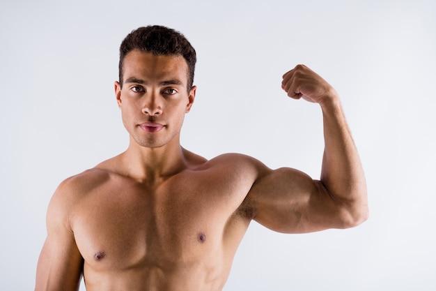 팔뚝을 보여주는 잘 생긴 근육질 스포츠맨 검은 피부 남자 이상적인 신체 구성의 사진
