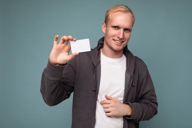 회색 스웨터와 파란색 배경 벽에 격리된 흰색 티셔츠를 입은 잘생긴 긍정적인 금발 남자의 사진이 신용카드를 들고 카메라를 바라보고 있습니다.