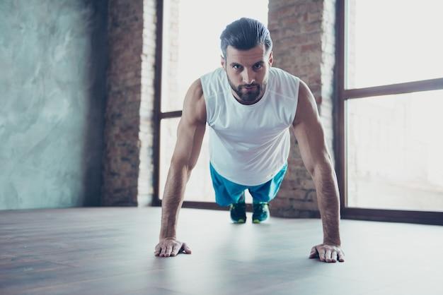Фотография красивого спортсмена-тренера, показывающего клиенту, как правильно делать отжимания и планку, руки, опирающиеся на пол, спортивная майка, окна тренировочного дома в помещении