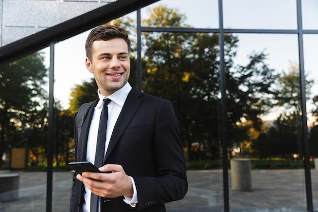 携帯電話を使用して通りで屋外を歩いているハンサムな青年実業家の写真。