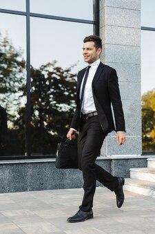 通りで屋外を歩いているハンサムな青年実業家の写真。