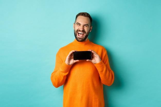 웃으면 서 청록색 배경 위에 주황색 스웨터에 서있는 휴대 전화 화면에 재미있는 것을 보여주는 행복 성인 남자의 사진.