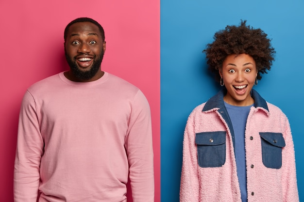 Фотография счастливой афро-американской пары стоят вплотную друг к другу, выражают положительные эмоции, радуются удивленному выражению лица, слышат отличные новости, вместе позируют на фоне розово-голубой стены.