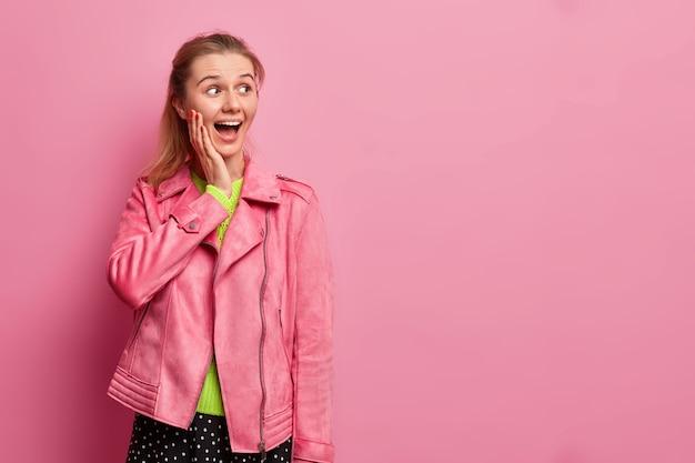 행복 한 놀란 젊은 여자의 사진은 뺨에 손을 유지합니다.