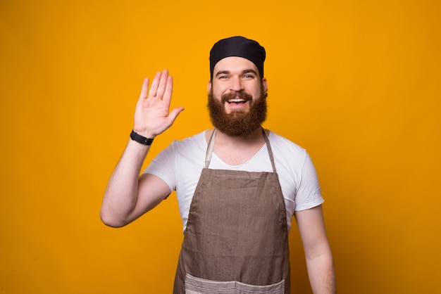 みんなに敬礼する幸せなひげを生やしたシェフの写真